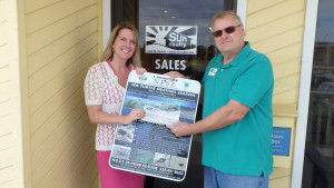 Ali Breaux of Sun Realty presents donation to N.E.S.T.