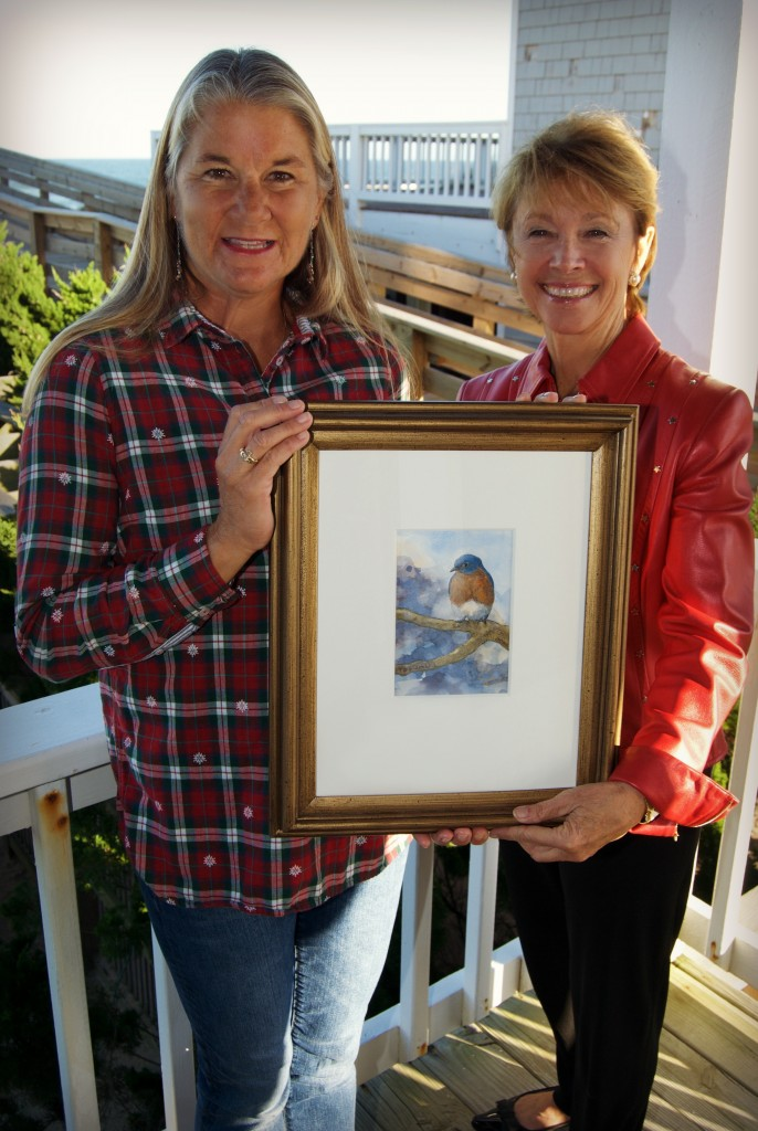 "Holly Robinson, N.E.S.T. Board member (right) presents Kim Stoltz, as the proud winner of the 2015 art raffle ""Between Heaven and Earth"" by E.M. Corsa."