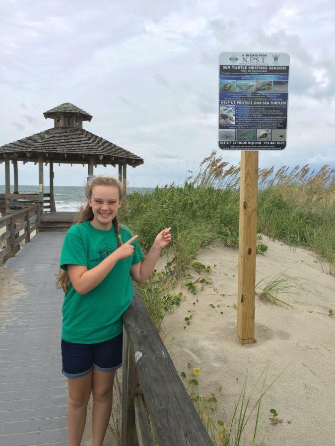 Ellen points out the NEST educational sign