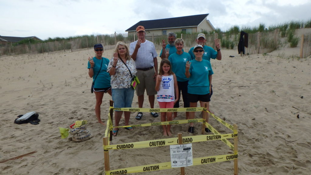 The smiling response team holds up 3 fingers to signify sea turtle nest #3