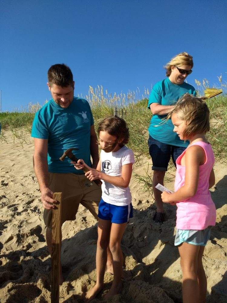 Our awesome NEST Jr. volunteers Tessa and Callie hammering in stakes with a little help from Dad!